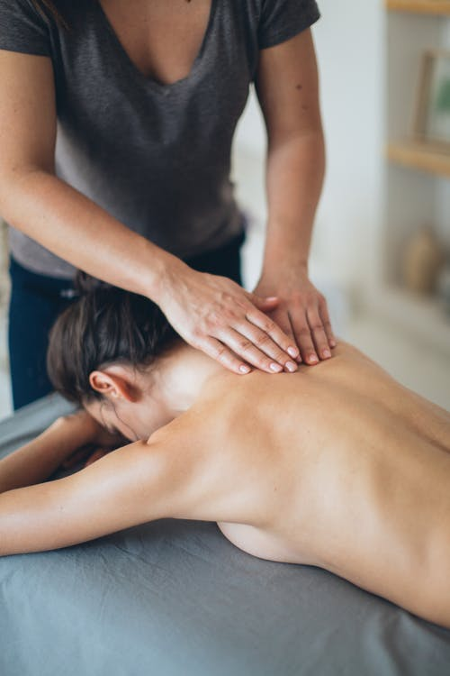 Crop masseuse massaging shoulder and back of client