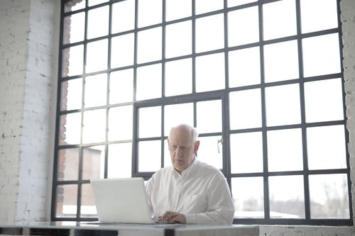 Man in White Shirt Sitting by the Table Using Macbook