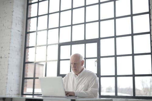Man in White Shirt Sitting in Front of Macbook