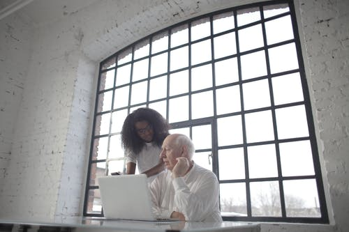 Professional aged male entrepreneur discussing startup project with young female African American colleague during office work with laptop and smartphone in workplace with industrial interior