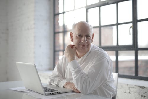 Positive bold aged male freelancer wearing formal shirt sitting at table with laptop and documents and looking at camera with smile during remote work in room with industrial interior