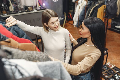 From above of young casually dressed women choosing warm puffer jacket in shop while standing near rails with clothes and discussing details
