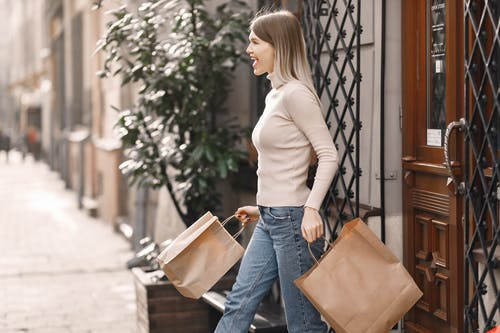 Expressive woman with bags coming out of shop