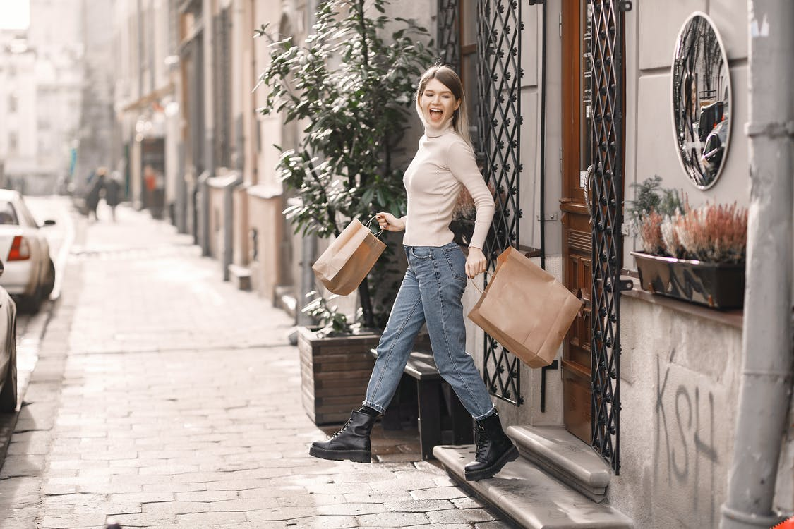 Side view of cheerful shouting woman in casual wear with shopping bags and boots stepping on stairs while coming out of store