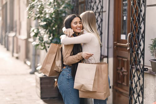 Side view of cheerful young women with shopping bags standing on city street near door while toothy smiling and hugging