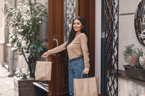 Woman In Brown Long Sleeves And Blue Denim Jeans Holding Brown Paper Bags
