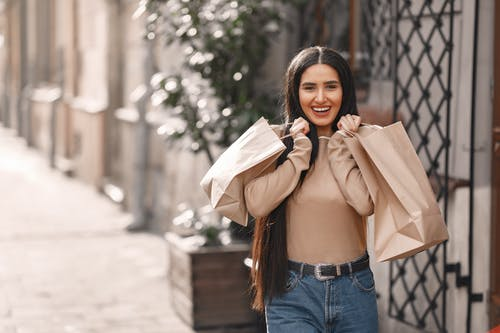 Positive female shopaholic with bags smiling at camera on street