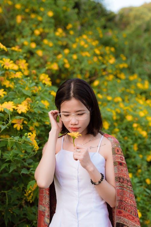 Mujer En Camiseta Blanca Sin Mangas Sosteniendo Una Flor Amarilla