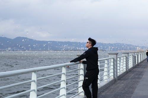 Man in Black Hoodie and Black Pants Holding Metal Railings Looking at the Sea