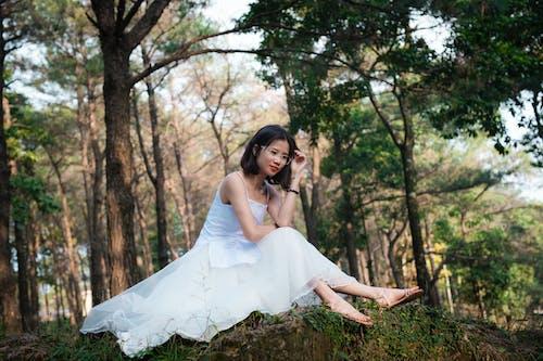 Kobieta W Białej Sukni W Okularach Siedzi Pod Drzewem