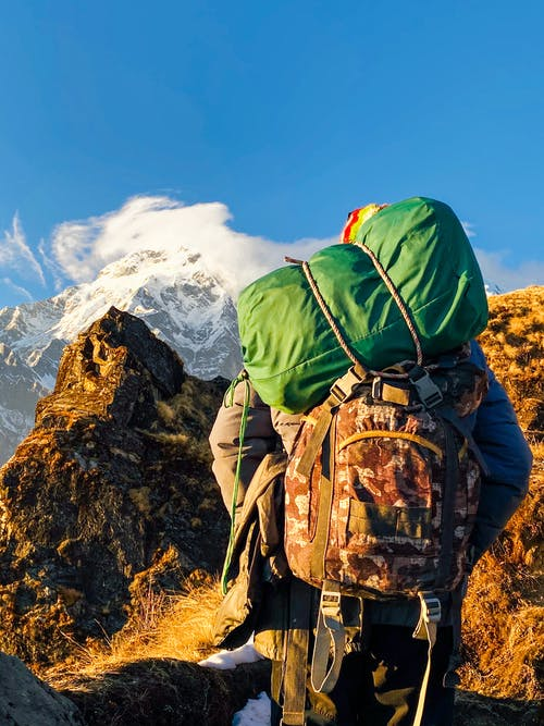 Anonymous hiker exploring mountainous terrain on sunny day