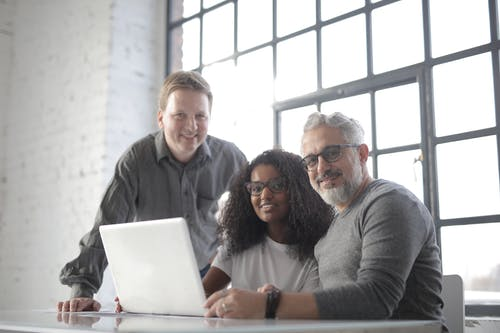 Smiling multiracial coworkers working on laptop in modern workspace