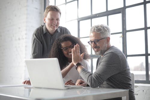 Positive coworkers of different ages in casual wear cheering up each other  while surfing Internet on laptop in light workplace