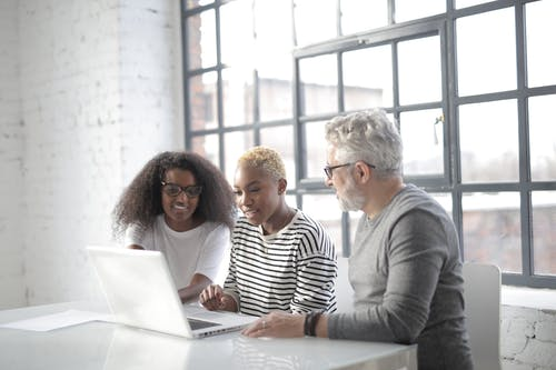 Positive multiracial colleagues working on computer together in modern workplace
