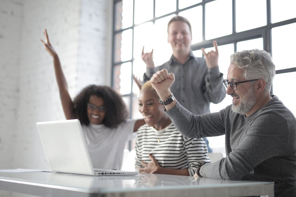 Cheerful multiethnic friends with laptop raising hands in success