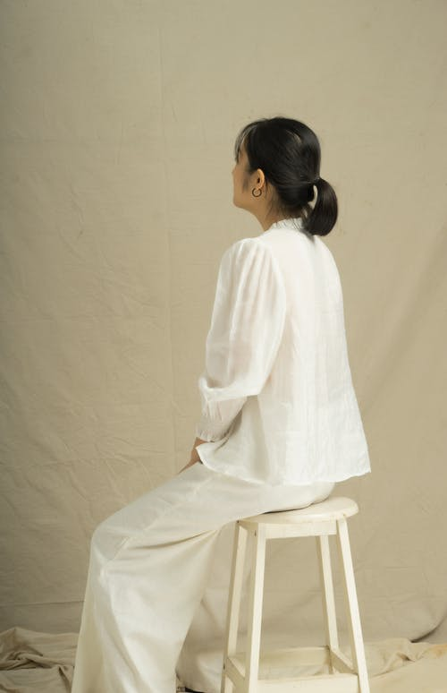 Woman in White Long Sleeve Dress Sitting on White Wooden Chair