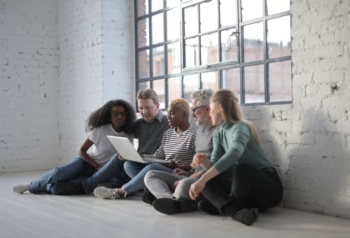 Group of diverse people using laptop together
