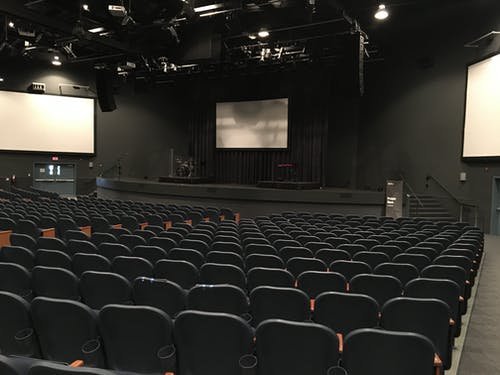 Empty cinema theater hall with black chairs and monitors