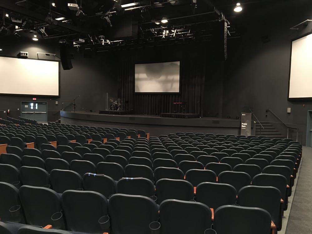 Rows of comfortable empty seats in modern theater hall with stage and screens