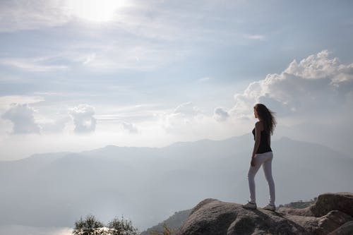 Woman Standing On A Rock Looking At Nature's View