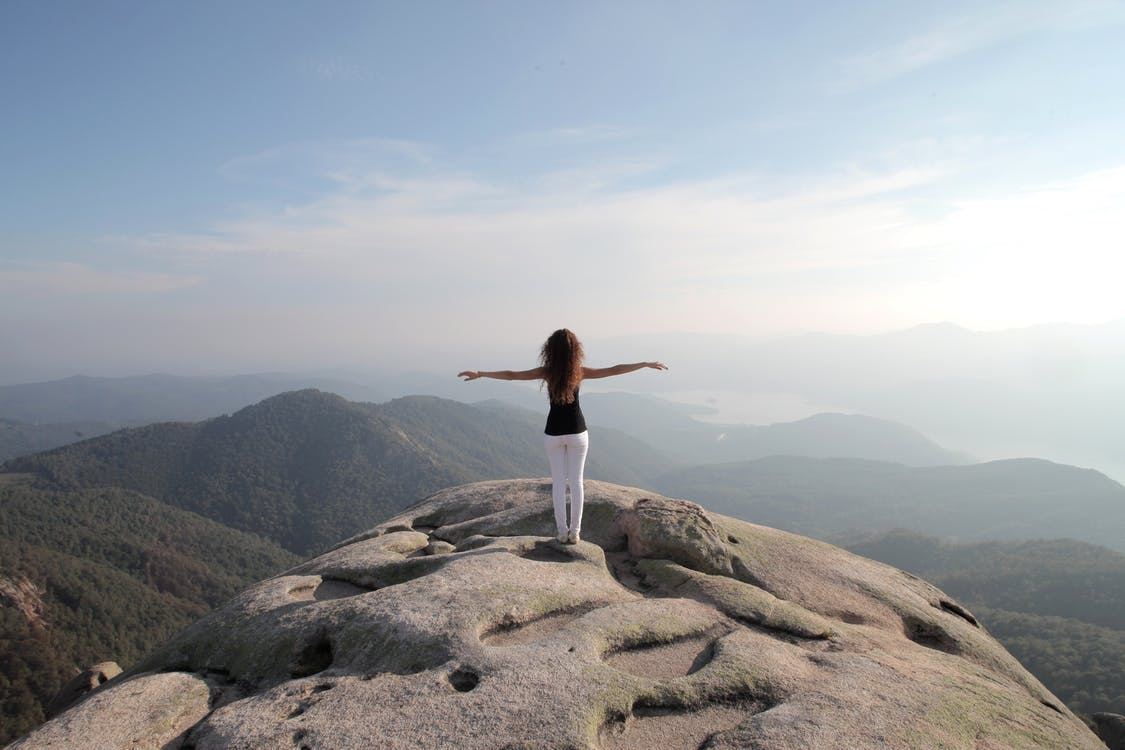 Woman In Black Tank Top And White Pants Standing On Rock
