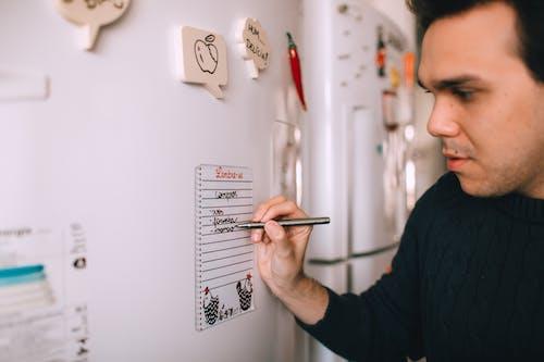 Young man writing reminder on fridge note