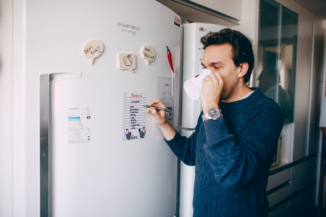 Young man writing reminder on fridge and drinking coffee at home