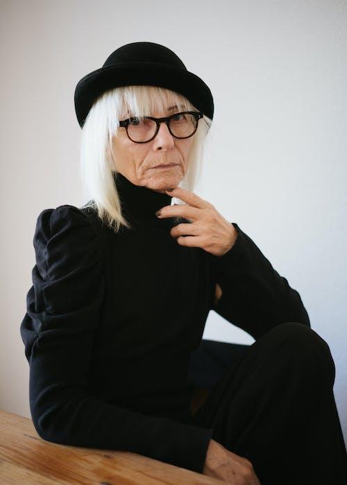 Woman in Black Long Sleeve Sweater Wearing Black Hat and Eyeglasses
