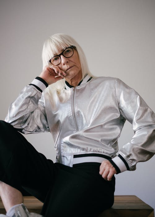 Woman in White Letterman Jacket Wearing Eyeglasses Sitting on Table
