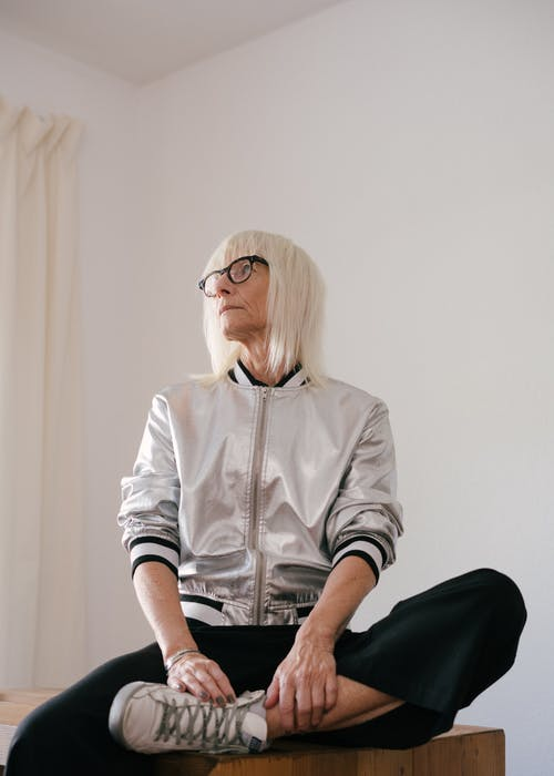 Woman in White Letterman Jacket and Black Pants Wearing Eyeglasses Sitting on Table