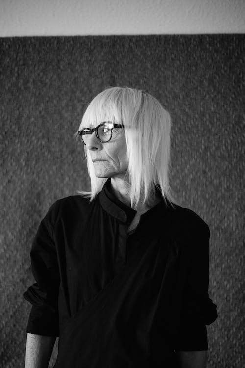Grayscale Photo of Woman in Black Jacket Wearing Eyeglasses