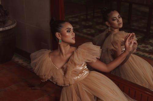 鏡の近くの床に座っている優雅な若い女性