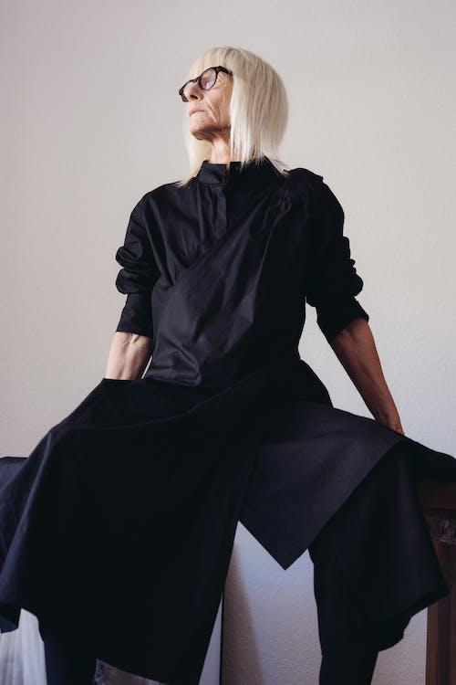 Elderly Woman in Black Long Sleeve Dress Wearing Eyeglasses Sitting on Table
