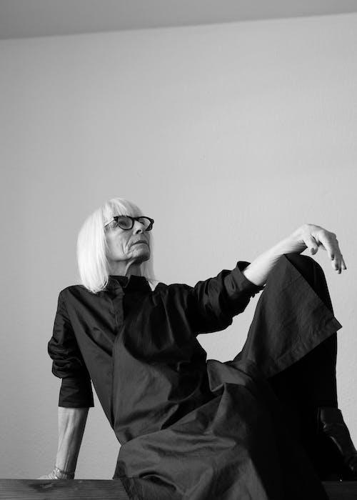 Gray-scale Photo of Woman in Black Long Sleeve Dress Wearing Eyeglasses