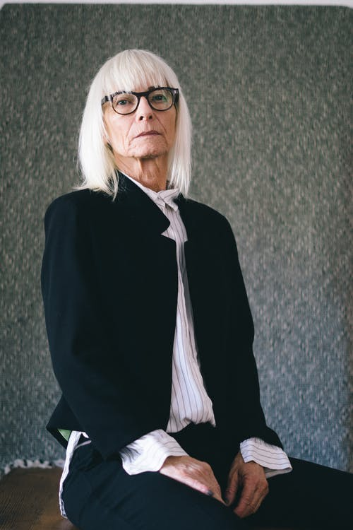 Old stylish female in black suit and white shirt