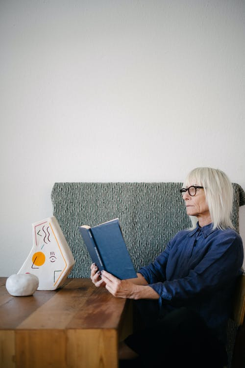Serious senior woman reading book in living room