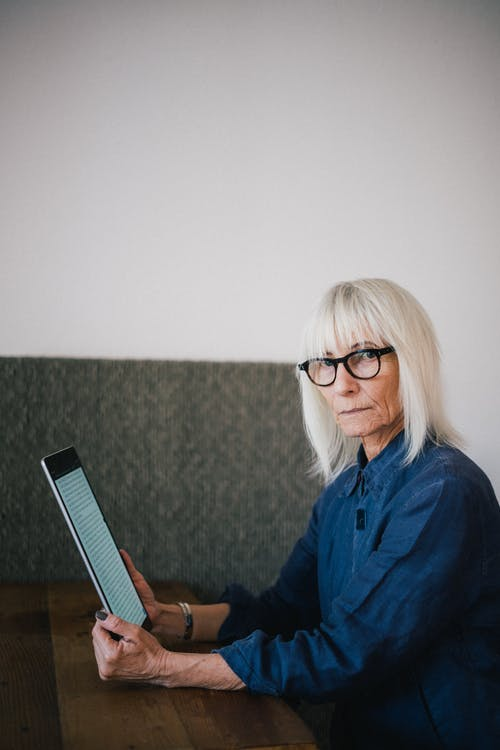 Old woman using tablet and looking at camera