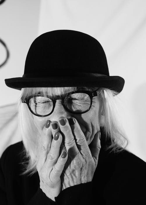 Gray scale Photo of Woman Wearing Fedora Hat and Eyeglasses Covering Her Mouth
