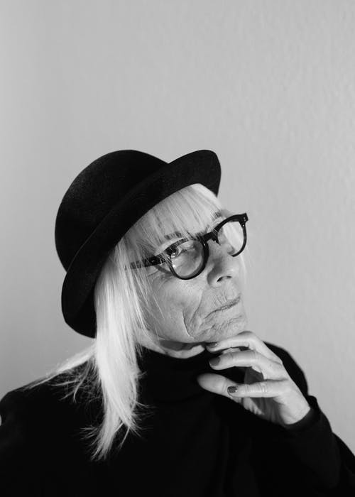 Gray scale Photo of Woman in Black Coat Wearing Black Hat and Eyeglasses