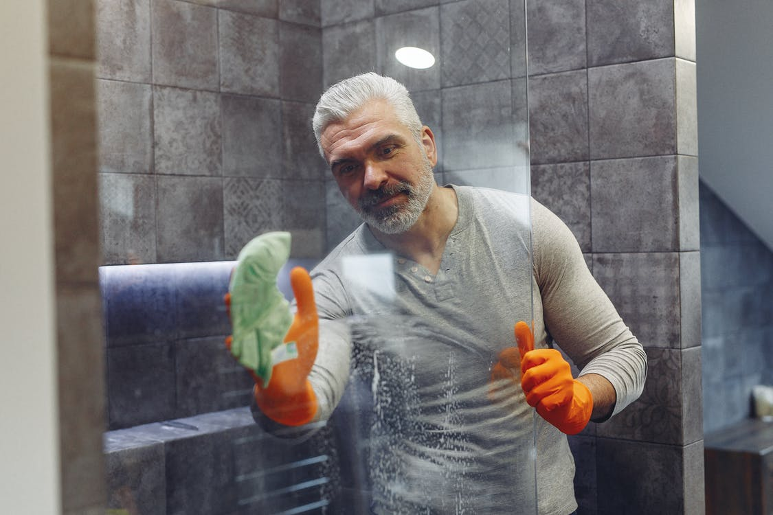 Happy grey haired man wiping glass in bathroom