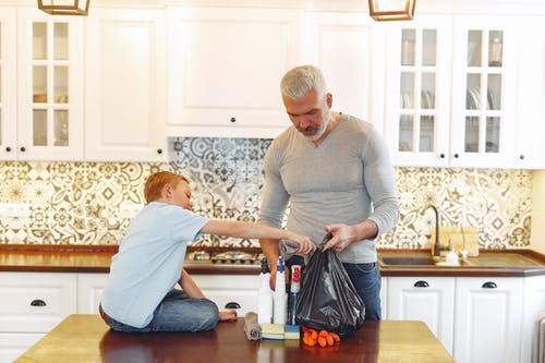 Grey haired dad with beard and small kid preparing cleaning stuff for tidying up kitchen