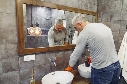 Back view of grey haired male with beard in orange rubber gloves attentively tidying up bathroom
