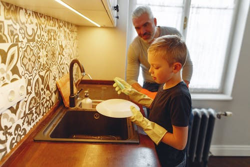 Father teaching son dishwashing at kitchen