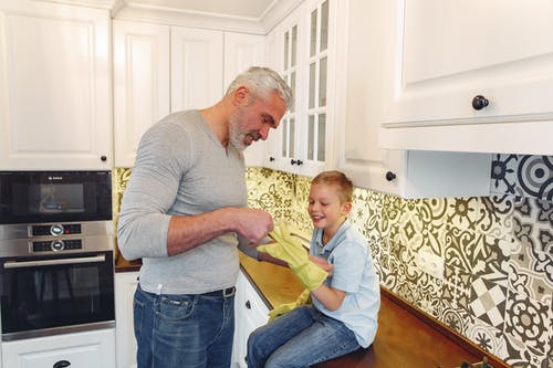 Side view of satisfied grey haired father with beard and smiling kid at kitchen