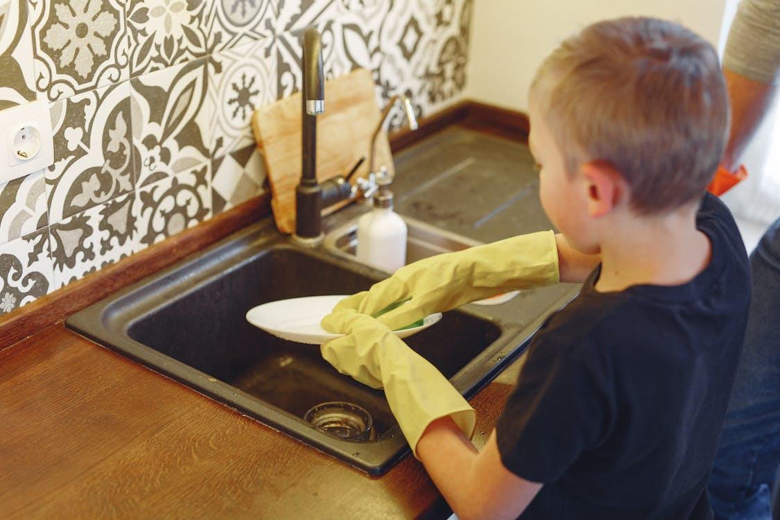 Small kid attentively dishwashing at kitchen