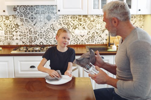 Side view of satisfied grey haired male with beard cleaning crockery with kid