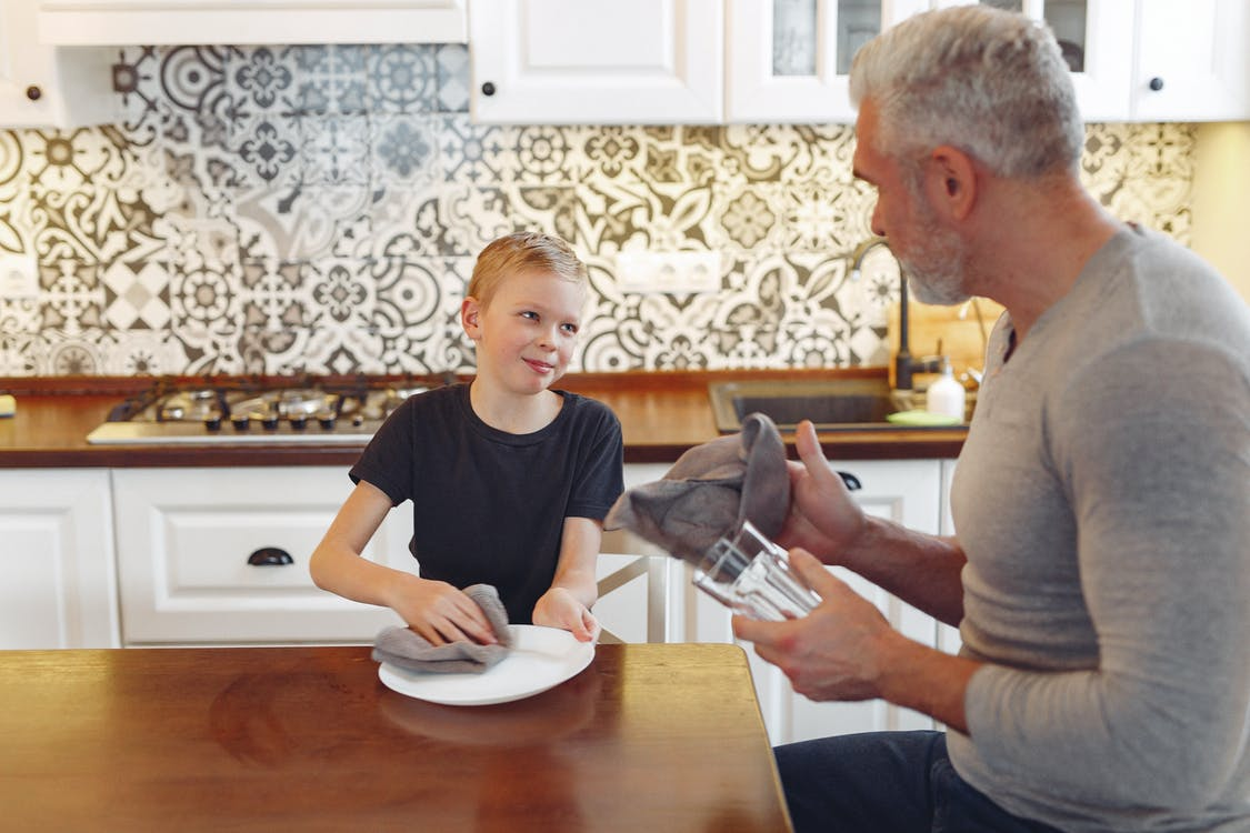 Happy father wiping tableware with son