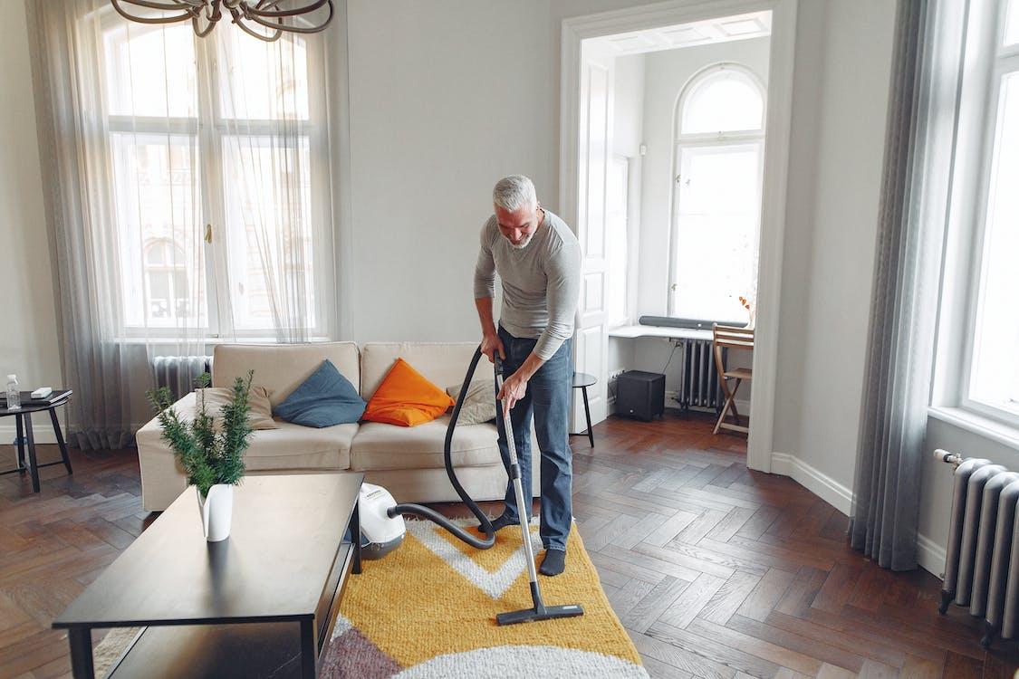 Tall man vacuuming floor at apartment