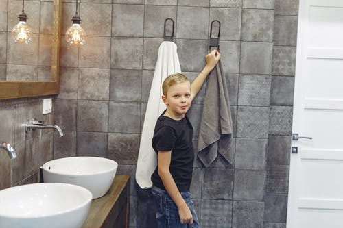 Boy with blond hair taking towel in tiled bathroom while looking at camera