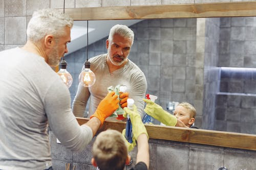 Father with son cleaning mirror in bathroom